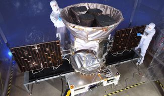 This undated photo made available by NASA shows technicians with the Transiting Exoplanet Survey Satellite (TESS). Scheduled for an April 2018 launch, the spacecraft will prowl for planets around the closest, brightest stars. These newfound worlds eventually will become prime targets for future telescopes looking to tease out any signs of life. (NASA via AP)