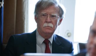 In this April 9, 2018 photo, National security adviser John Bolton listens as President Donald Trump speaks during a cabinet meeting at the White House in Washington. Bolton held talks Thursday with his South Korean and Japanese counterparts, as the U.S. gears up for an unprecedented summit with North Korea.  (AP Photo/Evan Vucci)