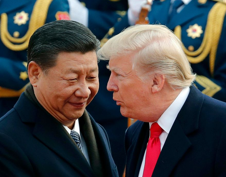FILE - In this Nov. 9, 2017, file photo, U.S. President Donald Trump, right, chats with Chinese President Xi Jinping during a welcome ceremony at the Great Hall of the People in Beijing. The Trump administration has once again declined to brand China a currency manipulator, but it did target that country and five others for special monitoring for what the administration says are practices that are worsening America's trade deficit. (AP Photo/Andy Wong, File)