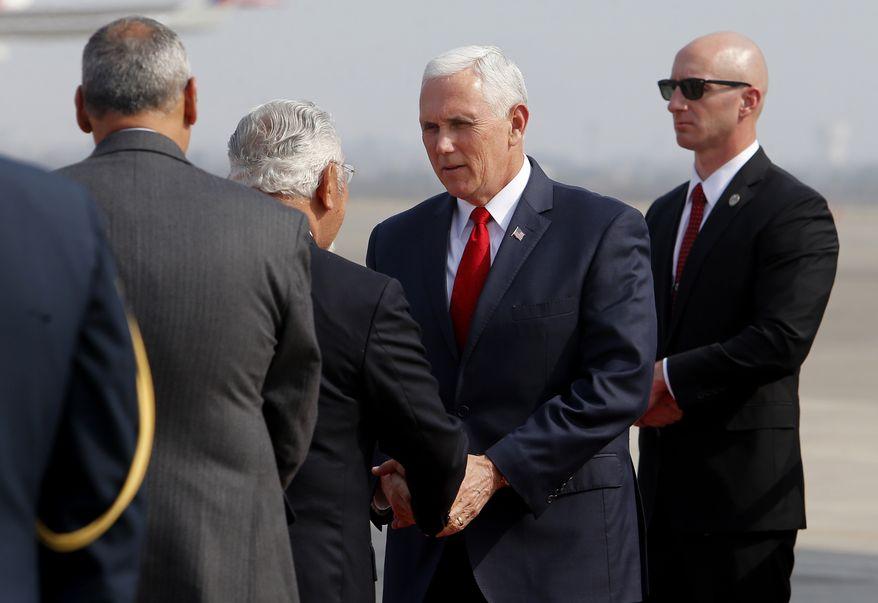 Il vicepresidente americano Mike Pence stringe la mano al ministro peruviano Javier Pique al suo arrivo all'aeroporto internazionale Jorge Chavez di Lima, in Perù, il 13 aprile 2018. Credits to: AP/Karel Navarro.