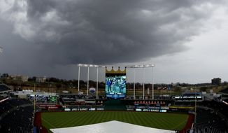 Grounds crew workers pull the tarp off the field after a storm dumped rain on Kauffman Stadium before a baseball game between the Kansas City Royals and the Los Angeles Angels ,Friday, April 13, 2018, in Kansas City, Mo. (AP Photo/Charlie Riedel)