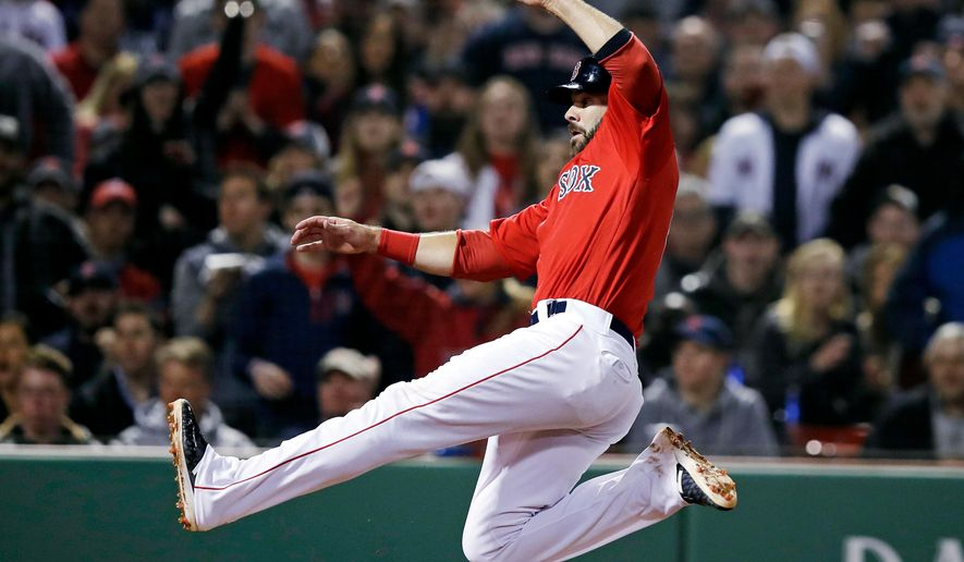 Boston Red Sox's Mitch Moreland leaps to slide as he scores on a wild pitch by Baltimore Orioles' pitcher Mike Wright Jr. during the sixth inning of a baseball game at Fenway Park in Boston, Friday, April 13, 2018. (AP Photo/Charles Krupa)