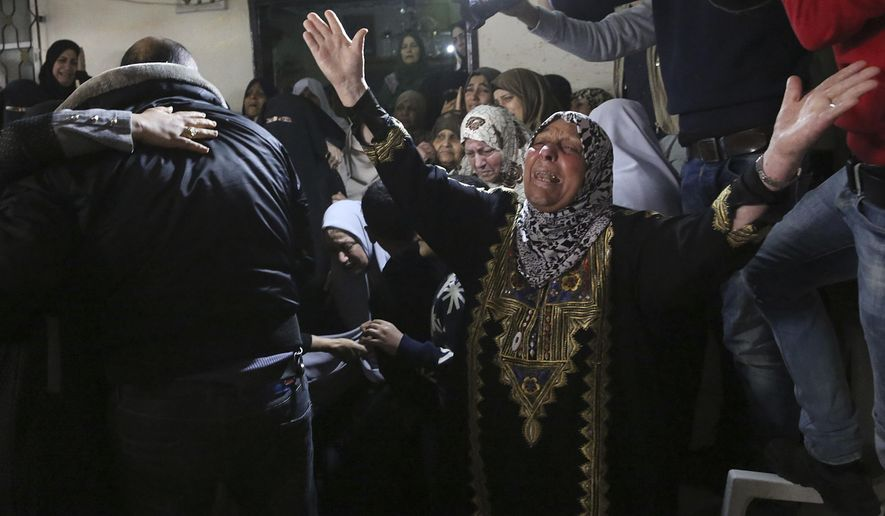 Relatives react while mourners carry the body of Mohammed Hajeleh, 30, who was killed early Thursday morning by an Israeli airstrike, at his family house during his funeral in Gaza City, Thursday, April 12, 2018. The Israeli military says it bombed a Hamas military target in the Gaza Strip hours after an explosive device detonated near an Israeli army vehicle on the border. (AP Photo/Adel Hana)