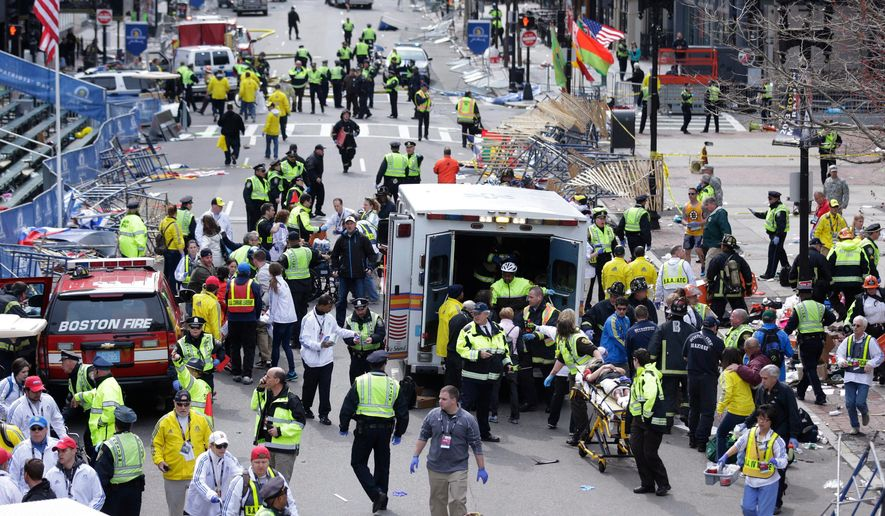 FILE - In this April 15, 2013 file photo, medical workers aid injured people following an explosion at the finish line of the 2013 Boston Marathon in Boston. Twin bombs near the finish line of one of the world's most storied races killed three people and injured 260 others, many of whom lost their legs, five years ago on April 15, 2013. (AP Photo/Charles Krupa, File)