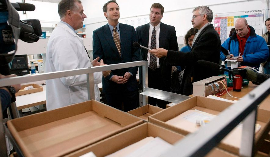 FILE - In this Nov. 12, 2003, file photo, CanadaDrugs.com Director of Pharmacy Robert Fraser, left, takes Minnesota Gov. Tim Pawlenty, second left, on a tour of the Internet pharmacy CanadaDrugs.com in Winnipeg, Manitoba in Canada. The Canadian online pharmacy is expected to be fined $34 million for importing counterfeit cancer drugs and other unapproved pharmaceuticals into the United States. Canada Drugs, which calls itself that nation's largest internet drugstore, and its founder, Kris Thorkelson, not seen, are being sentenced Friday, April 13, 2018, after pleading guilty to felony charges in the U.S. state of Montana. (AP Photo/Ruth Bonneville, File)