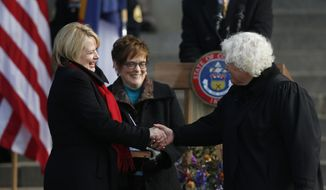 FILE - In this Jan. 13, 2015, file photo, Colorado's new attorney general Cynthia Coffman, left, shakes hands with Colorado Supreme Court Chief Justice Nancy E. Rice after Coffman took the oath of office during inauguration ceremony on the west steps of the Colorado State Capitol in Denver. Coffman is vying for the chance to run for the state's governorship at the Republican State Assembly Saturday, April 14, 2018, in Boulder, Colo. (AP Photo/David Zalubowski, File)