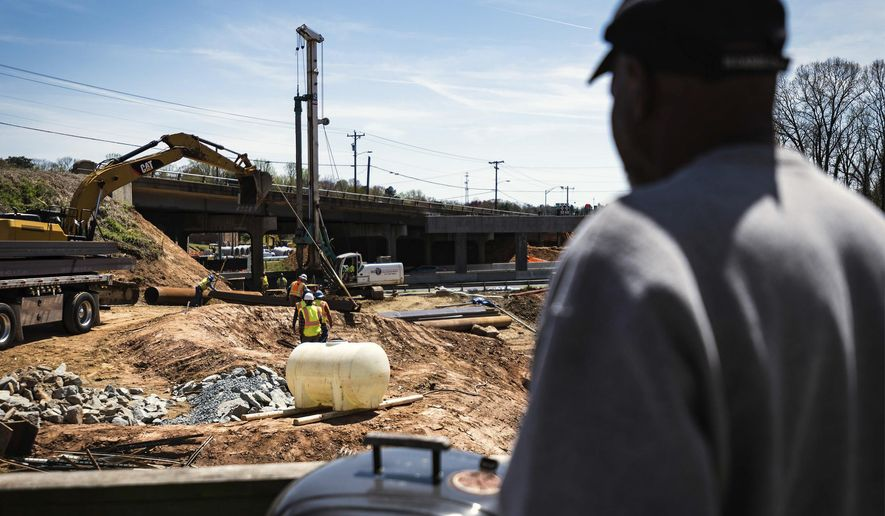 """Nathaniel Allen stands on his side porch right next to the Business 40 construction Thursday, April 5, 2018, on Westdale Avenue in Winston-Salem, N.C. Allen said there's too much dust from the roadwork to even think about using his outdoor grill. """"It gets noisy at times when they are drilling or blasting or something like that,"""" Allen said. """"It looks like they have a long way to go to get done."""" (Allison Lee Isley/The Winston-Salem Journal via AP)"""