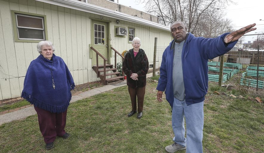 In a Tuesday, March 27, 2018 photo, Sister Margaret McKenna, left with Sister Sylvia Strahler, and Gary Robinson talk about the New Jerusalem Laura recovery Center Garden on Norris Street in North Philadelphia. Hundreds of recovering users such as Robbins have gone through New Jerusalem's program, and all have tended to the garden as part of a required two hours of daily community service.  (Steven M. Falk/The Philadelphia Inquirer via AP)
