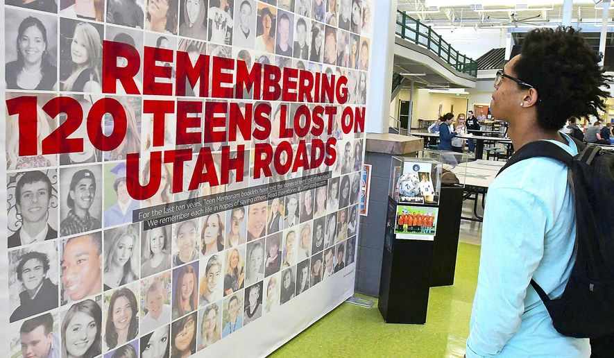 In this Monday, April 9, 2018 photo, Abraham Masoperah looks at a display at Green Canyon High School in North Logan, Utah, that showed teenagers who died from auto accidents along Utah roads. (Eli Lucero/The Herald Journal via AP)