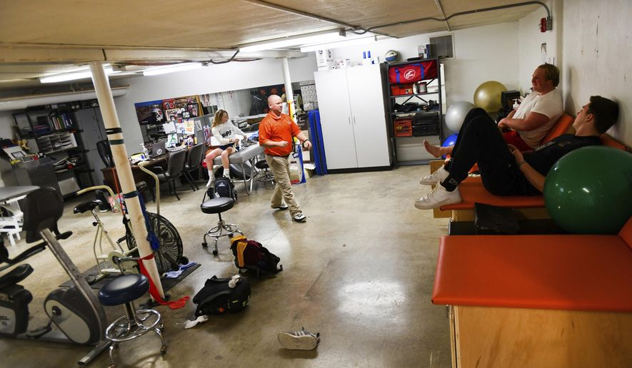 In this March 14, 2018 photo Kyle Geirnaeirt, center, a full-time athletic trainer at Washington  Community High School, in Washington, Ill., works in a room converted for rehabbing student athletes. Thanks to generous funding from the school, the 12th Man Booster Club and alumni organization, Geirnaeirt now works full-time for the Washington Panthers through Midwest Orthopaedic Center. (Ron Johnson/Journal Star via AP)