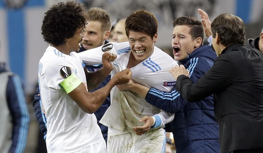 Marseille's Hiroki Sakai, center, is congratulated by teammates at the end to their Europa League quarter final second leg soccer match against RB Leipzig at the Velodrome stadium in Marseille, southern France, Thursday, April 12, 2018. Marseille defeated Leipzig 5-2. (AP Photo/Claude Paris)