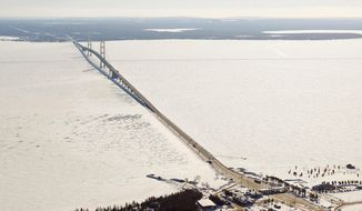 FILE - This Feb. 11, 2014, aerial file photo shows a view of the Mackinac Bridge, which spans a 5-mile-wide freshwater channel called the Straits of Mackinac that separates Michigan's upper and lower peninsulas. Sen. Gary Peters of Michigan said Friday, April 13, 2018, that the flow of crude oil through twin pipelines through the Straits should be suspended until authorities determine how severely they were damaged by what may have been a ship anchor strike. The Coast Guard is delaying action because of a heavy storm expected this weekend. (Keith King/Traverse City Record-Eagle via AP, Pool, File)