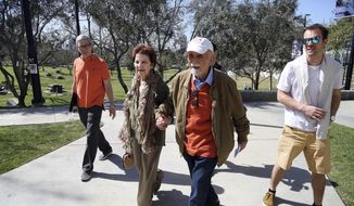 In this Wednesday, April 11, 2018, photo, childhood Holocaust survivors Simon Gronowski, center right, and Alice Gerstel Weit hold hands as they tour the Los Angeles Holocaust Museum. After the Nazis invaded Belgium, they hid together in the Gronowski family's home before the Gerstel family fled on a perilous journey that eventually led them to the United States. Gronowski's family stayed behind, and his mother and sister died at Auschwitz. For 76 years Gerstel Weit didn't know Gronowski was the family's only survivor. Her son Dann Netter is at left; his grandson Romain De Nys at right. (AP Photo/Reed Saxon)