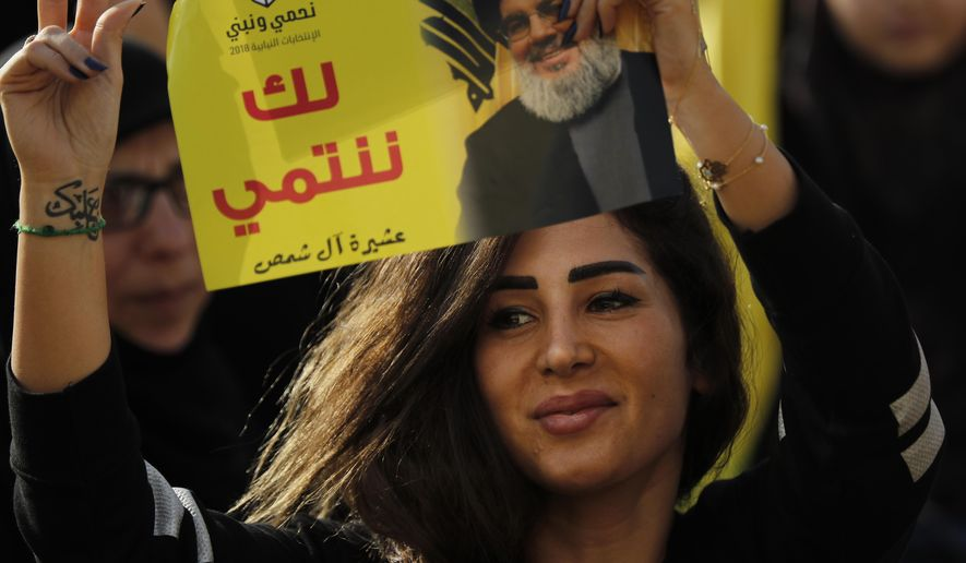 "A supporter of Hezbollah leader Sayyed Hassan Nasrallah holds up his portrait with Arabic words that read: ""We belong with you,"" during an election campaign speech in a southern suburb of Beirut, Lebanon, Friday, April 13, 2018. Nasrallah says Monday's attack on the T4 air base ushers in a new phase that puts Israel in a state of ""direct confrontation"" with the Islamic Republic of Iran. (AP Photo/Hussein Malla)"