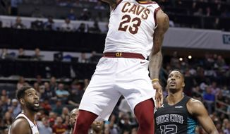 FILE - In this March 28, 2018, file photo, Cleveland Cavaliers' LeBron James (23) dunks past Charlotte Hornets' Dwight Howard (12) during the second half of an NBA basketball game in Charlotte, N.C. James, who will try to lead the Cleveland Cavaliers to their fourth straight NBA Finals, just completed the 15th regular season of his career, and it may have been his best yet. (AP Photo/Chuck Burton, File)