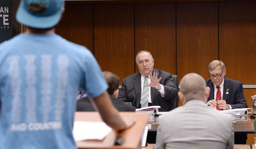 John Engler, center, interim President of Michigan State University, tells Dan Martel, 21, President of MSU college democrats, that his allotted speaking time of five minutes is up during a university board meeting, Friday, April 13, 2018, Lansing, Mich. Engler said Friday that he regrets the school's response to a woman filing a federal rape lawsuit against the university.  (Clarence Tabb Jr./Detroit News via AP)