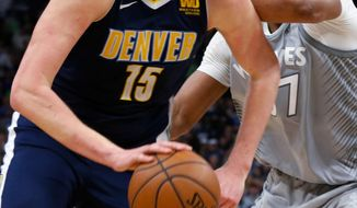 Denver Nuggets' Nikola Jokic, left, drives as Minnesota Timberwolves' Taj Gibson defends during the second half of an NBA basketball game Wednesday, April 11, 2018, in Minneapolis. The Timberwolves won 112-106 in overtime, making the playoffs. (AP Photo/Jim Mone)