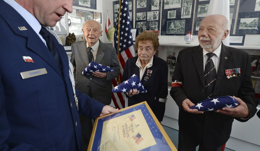 U.S. Embassy in Warsaw Defense Attache Col. John Downey, left, reads a diploma during an emotional ceremony in which he presented U.S. flags in a sign of recognition to three veterans of World War II and 1944 Warsaw Rising, l-r, Col. Eugeniusz Tyrajski, Col. Halina Jedrzejewska and Col. Zbigniew Galperyn, in Oswiecim, Poland, Friday, April 13, 2018. (AP Photo/Czarek Sokolowski)
