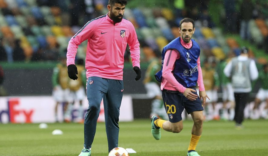 Atletico's Diego Costa, left, warms up with his teammate Atletico's Juanfran prior to the start of he Europa League quarterfinal second leg soccer match between Sporting CP and Atletico Madrid at the Alvalade stadium in Lisbon, Thursday, April 12, 2018. (AP Photo/Armando Franca)