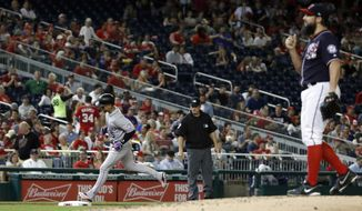 Colorado Rockies' Carlos Gonzalez (5) rounds third base on a solo home run off Washington Nationals starting pitcher Tanner Roark, right, during the fourth inning of a baseball game at Nationals Park, Friday, April 13, 2018, in Washington. (AP Photo/Alex Brandon)