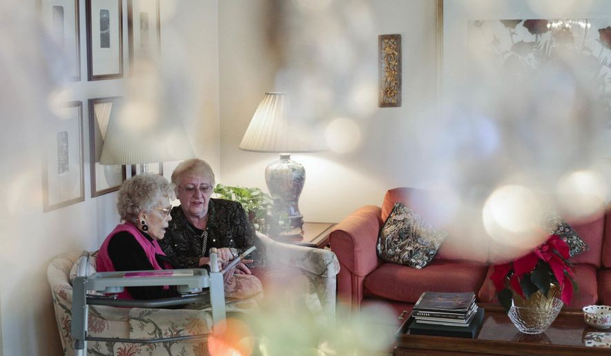 This photo taken Jan. 5, 2018, shows Marian Christensen, left, and Felicity Varkevisser writing a list for grocery shopping in Christensen's home in Provo, Utah. Christensen lives alone in her home and is turning 98-years-old next month. (Evan Cobb/The Daily Herald via AP)