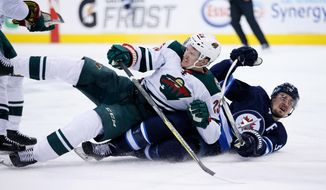 Minnesota Wild's Jonas Brodin (25) hauls down Winnipeg Jets' Mark Scheifele (55) during the second period of Game 2 of an NHL hockey first-round playoff series Friday, April 13, 2018, in Winnipeg, Manitoba. Brodin was called for a penalty. (John Woods/The Canadian Press)