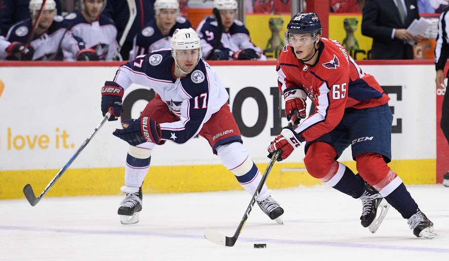 Washington Capitals left wing Andre Burakovsky (65) skates with the puck against Columbus Blue Jackets center Brandon Dubinsky (17) during the first period in Game 1 of an NHL first-round hockey playoff series, Thursday, April 12, 2018, in Washington. (AP Photo/Nick Wass)