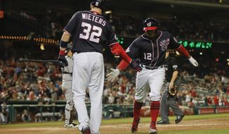 Washington Nationals second baseman Howie Kendrick (12) is greeted by teammate Matt Wieters (32) after hitting a solo homer off Colorado Rockies starting pitcher Chad Bettis (35) in the fifth inning of a baseball game at Nationals Park, Thursday, April 12, 2018, in Washington. (AP Photo/Pablo Martinez Monsivais)