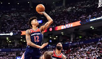 Washington Wizards forward Kelly Oubre Jr. (12) shoots over Toronto Raptors center Jakob Poeltl (42) as Wizards forward Markieff Morris (5) watches during the second half of Game 1 of an NBA basketball first-round playoff series in Toronto on Saturday, April 14, 2018. (Frank Gunn/The Canadian Press via AP) **FILE**