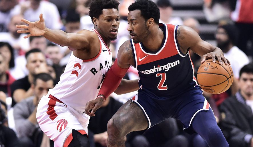 Washington Wizards guard John Wall (2) protects the ball from Toronto Raptors guard Kyle Lowry (7) during the first half of a first-round NBA basketball playoff series in Toronto, Saturday, April 14, 2018. (Frank Gunn/The Canadian Press via AP)