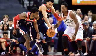 Washington Wizards guard John Wall (2) and forward Otto Porter Jr. (22) and Toronto Raptors guard DeMar DeRozan (10) vie for the ball during the second half of Game 1 of an NBA basketball first-round playoff series in Toronto on Saturday, April 14, 2018. (Frank Gunn/The Canadian Press via AP)