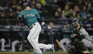 Seattle Mariners' Mitch Haniger watches his three-run home run in front of Oakland Athletics catcher Jonathan Lucroy during the seventh inning of a baseball game, Friday, April 13, 2018, in Seattle. (AP Photo/Ted S. Warren)