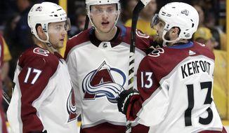 Colorado Avalanche center Alexander Kerfoot (13) celebrates with Tyson Jost (17) and Mikko Rantanen (96), of Finland, after scoring a goal against the Nashville Predators during the third period in Game 2 of an NHL hockey first-round playoff series Saturday, April 14, 2018, in Nashville, Tenn. (AP Photo/Mark Humphrey)