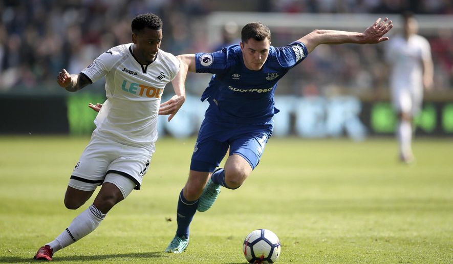 Swansea City's Luciano Narsingh, left, and Everton's Michael Keane battle for the ball during their English Premier League occer match at the Liberty Stadium, Swansea, Wales, Saturday, April 14, 2018. (Nick Potts/PA via AP)