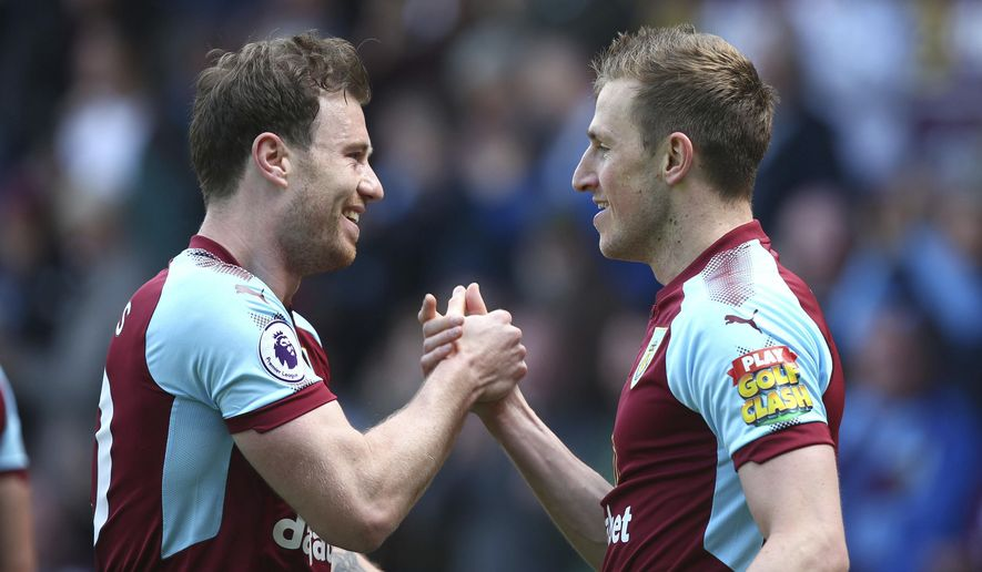 Burnley's Chris Wood, right, celebrates scoring his side's first goal of the game with team mate Ashley Barnes during the English Premier League soccer match between Burnley and Leicester City at Turf Moor stadium, Burnley, England. Saturday, April 14, 2018, 2018. (Dave Thompson/PA via AP)