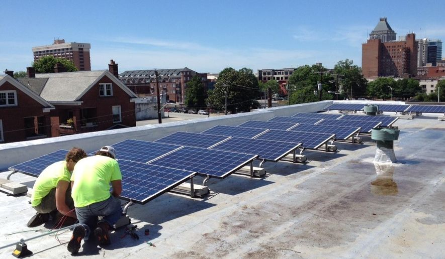 """In this June 3, 2015 photo made available by NC WARN, workers install a solar power system on the roof of Faith Community Church in Greensboro, NC. The installation and the electricity the panels generated prompted a dispute being considered by the North Carolina Supreme Court that will be heard on Tuesday, April 17, 2018. State utilities regulators have ruled the group that funded the $20,000 cost of the solar panels violated state law protecting regulated monopoly electric utilities was illegally producing electricity """"for the public."""" The group, NC WARN, says it was an allowable private power agreement with the church alone. ( NC WARN via AP)"""