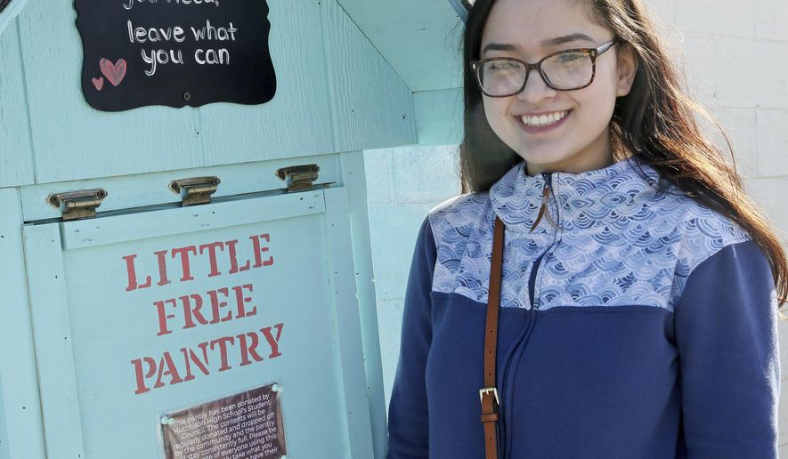 In this April 3, 2018 photo, Hutchison High School student body president Michelle Kougl poses next to the Little Free Pantry outside the Fairbanks Native Association Community Services building in Fairbanks, Alaska. Little Free Pantry is a nationwide movement based on the Little Free Library kiosks. But instead of books, Little Free Pantry is a place where people in need can find basic staples, and people with extra can share. (Eric Engman/Fairbanks Daily News-Miner via AP)