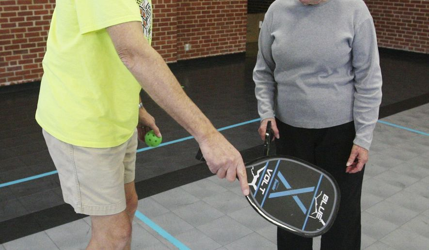 In this April 4, 2018 photo, Ron Haase teaches Jane Miller pickleball rules before they begin playing at the City of Hastings Community Center in Hastings, Neb. Pickleball has been a hit since the Hastings Parks and Recreation Department introduced the game late last year. (Amy Roh/The Hastings Tribune via AP)
