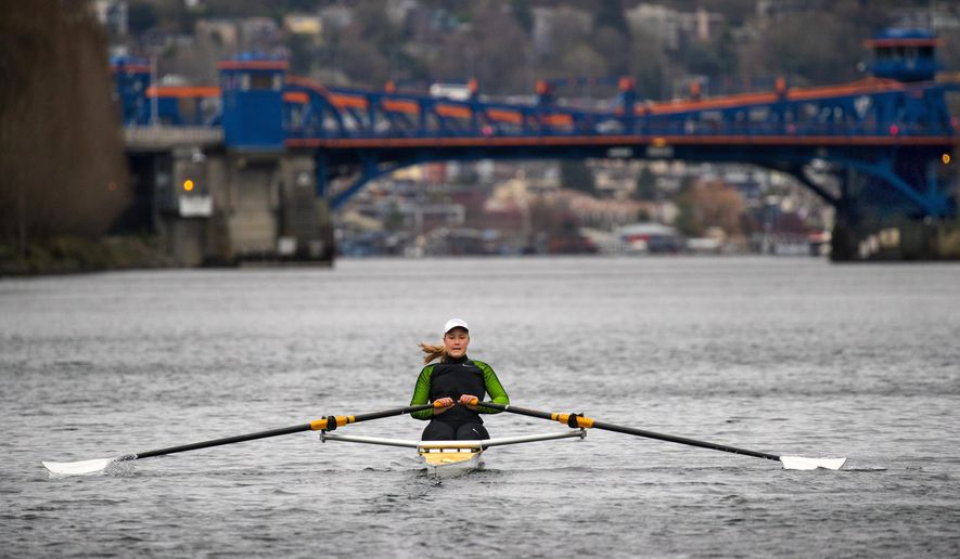 In a Thursday, March, 29, 2018 photo, Eliza Dawson Dawson trains at the Seattle Rowing Center and spends hours each day rowing in waters including this part of the Fremont Cut toward the Fremont Bridge, in Seattle, Wash. a former UW crew member, is part of a four-woman team that will row across the Pacific to Hawaii this June. She and her team want to try to break the record for women rowers.  (Mike Siegel/The Seattle Times via AP)