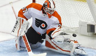 Philadelphia Flyers goaltender Brian Elliott blocks a shot during the first period in Game 2 of an NHL first-round hockey playoff series against the Pittsburgh Penguins in Pittsburgh, Friday, April 13, 2018. (AP Photo/Gene J. Puskar)
