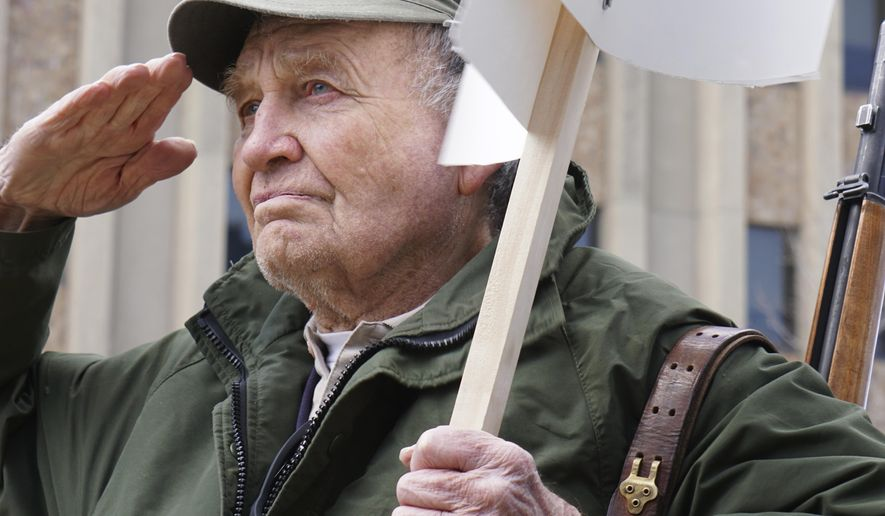 Roy Fansler stands with an M1 Garand rifle at a gun rally Saturday, April 14, 2018, in front of the Wyoming Supreme Court in Cheyenne, Wyo. About 100 people took part including a handful openly carrying firearms. (AP Photo/Mead Gruver)