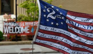 People participate in a gun rights rally as a Second Amendment flag is carried at the state capitol, Saturday, April 14, 2018, in Atlanta. About 40 gun rights supporters have gathered for one of dozens of rallies planned at statehouses across the U.S. (AP Photo/Mike Stewart) ** FILE **