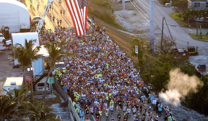 In this aerial photo provided by the Florida Keys News Bureau, about 1,500 runners cross the start line during the Seven Mile Bridge Run Saturday, April 14, 2018, near Marathon, Fla. The race over the convergence of the Atlantic Ocean and Gulf of Mexico was initiated in 1982 to mark the completion of a federally funded bridge rebuilding program to replace 37 aging spans originally built in the early 1900s to carry railroad trains. (Bob Care/Florida Keys News Bureau via AP)