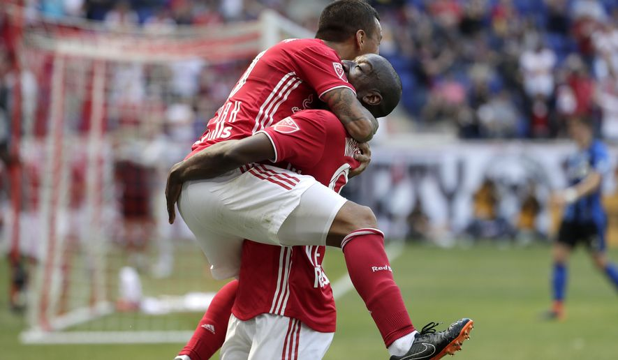 New York Red Bulls midfielder Alejandro Romero Gamarra, left, jumps on teammate forward Bradley Wright-Phillips after scoring a goal on the Montreal Impact during the second half of a soccer match, Saturday, April 14, 2018, in Harrison, N.J. (AP Photo/Julio Cortez)