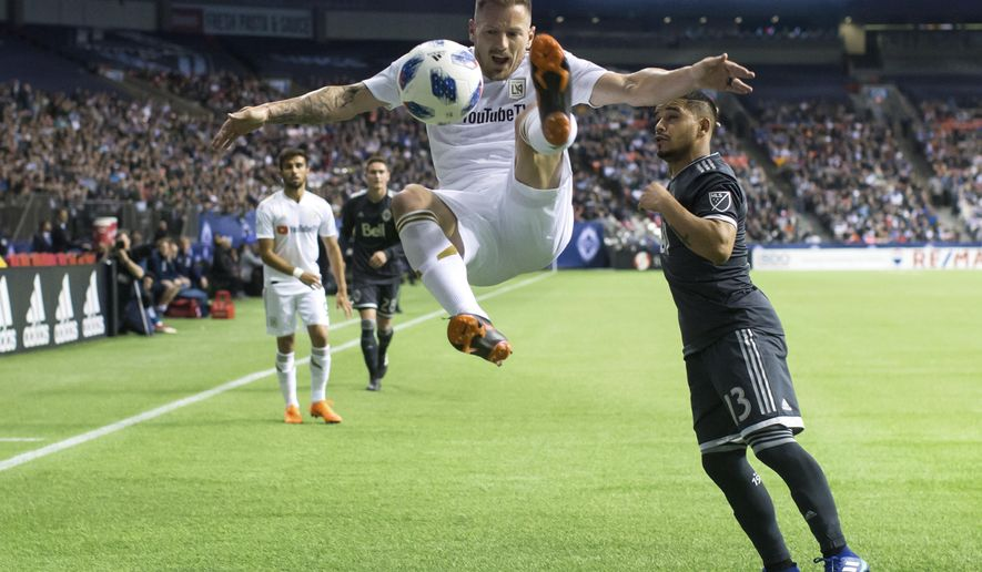 Los Angeles FC's Jordan Harvey, front, jumps to try and kick the ball away from Vancouver Whitecaps' Cristian Techera, right, during the second half of an MLS soccer match Friday, April 13, 2018, in Vancouver, British Columbia. (Darryl Dyck/The Canadian Press via AP)