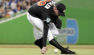 Miami Marlins relief pitcher Brad Ziegler bobbles a ball hit by Pittsburgh Pirates' Corey Dickerson to score Starling Marte during the ninth inning of a baseball game, Saturday, April 14, 2018, in Miami. (AP Photo/Lynne Sladky)