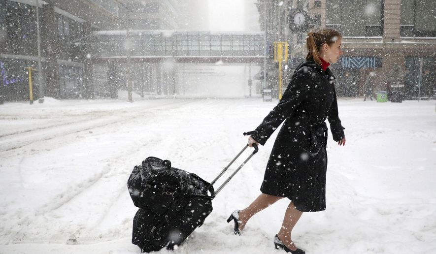 Delta Airlines flight attendant Victoria Flees trudges through the snow with her bags in downtown Minneapolis on the way back home from the light rail station after her flight to Paris was grounded along with all other planes at MSP because of weather, Saturday, April 14, 2018. The National Weather Service predicts 9 to 15 inches of snow across a large swath of southern Minnesota including the Twin Cities before it's all over. (Anthony Souffle/Star Tribune via AP)