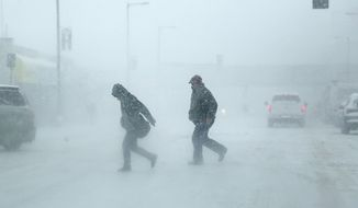 Pedestrians cross Nicollet Ave., running to catch a bus during a snowstorm in Minneapolis, Minn., Saturday, April 14, 2018. The National Weather Service predicts 9 to 15 inches of snow across a large swath of southern Minnesota including the Twin Cities before it's all over. (David Joles/Star Tribune via AP)