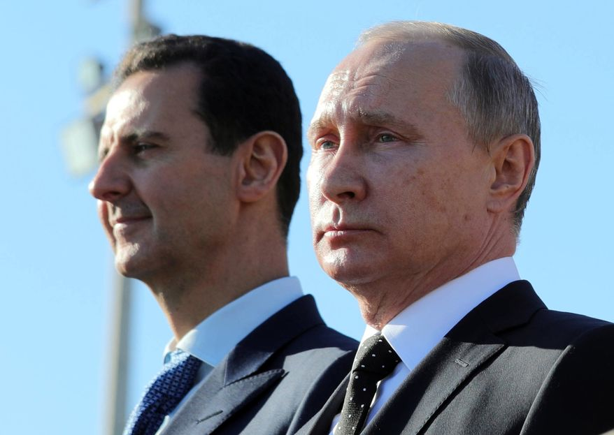 Russian President Vladimir Putin, right, and Syrian President Bashar Assad watch the troops marching at the Hemeimeem air base in Syria, on Monday, Dec. 11, 2017. Declaring a victory in Syria, Putin on Monday visited a Russian military air base in the country and announced a partial pullout of Russian forces from the Mideast nation. (Mikhail Klimentyev, Sputnik, Kremlin Pool Photo via AP)