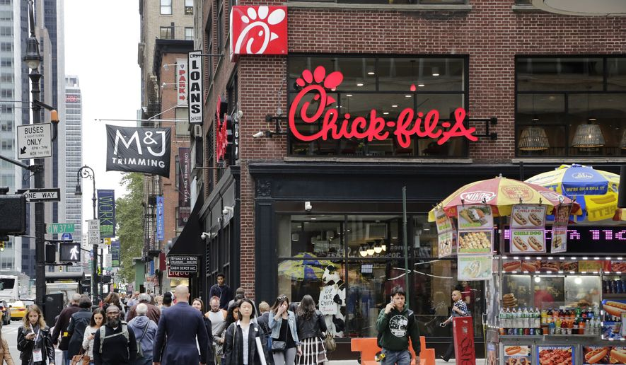 People walk past a new Chick-fil-A restaurant, Thursday, Oct. 1, 2015 in New York. The Atlanta-based privately held franchise company has more than 1900 restaurants in 41 states and Washington, D.C. The New York franchise, located a few blocks from Times Square, opens Saturday, Oct. 3, marking its push to become a bigger national player.  (AP Photo/Mark Lennihan)